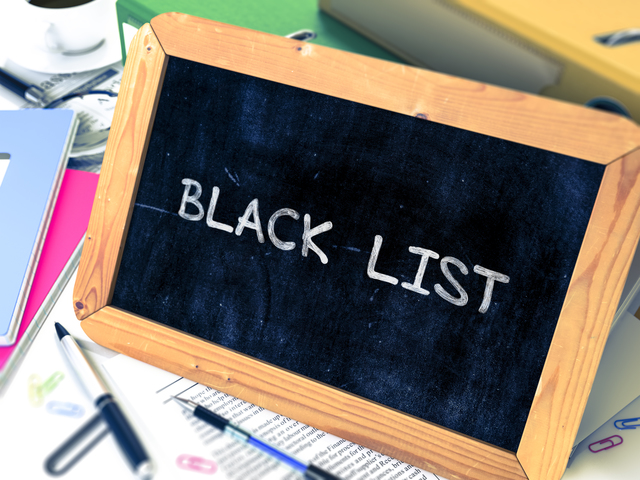 Black List Concept Hand Drawn on Chalkboard on Working Table Background. Blurred Background. Toned Image. 3D Render.